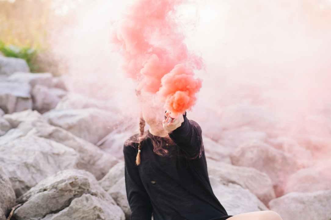 woman holding color smoke grenade