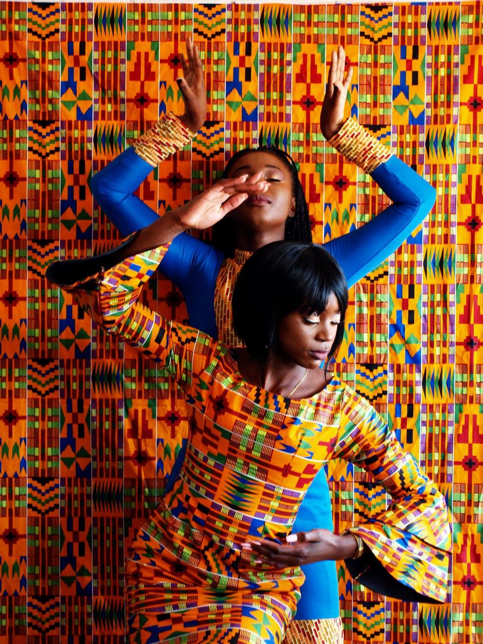 two women in dress near painted wall