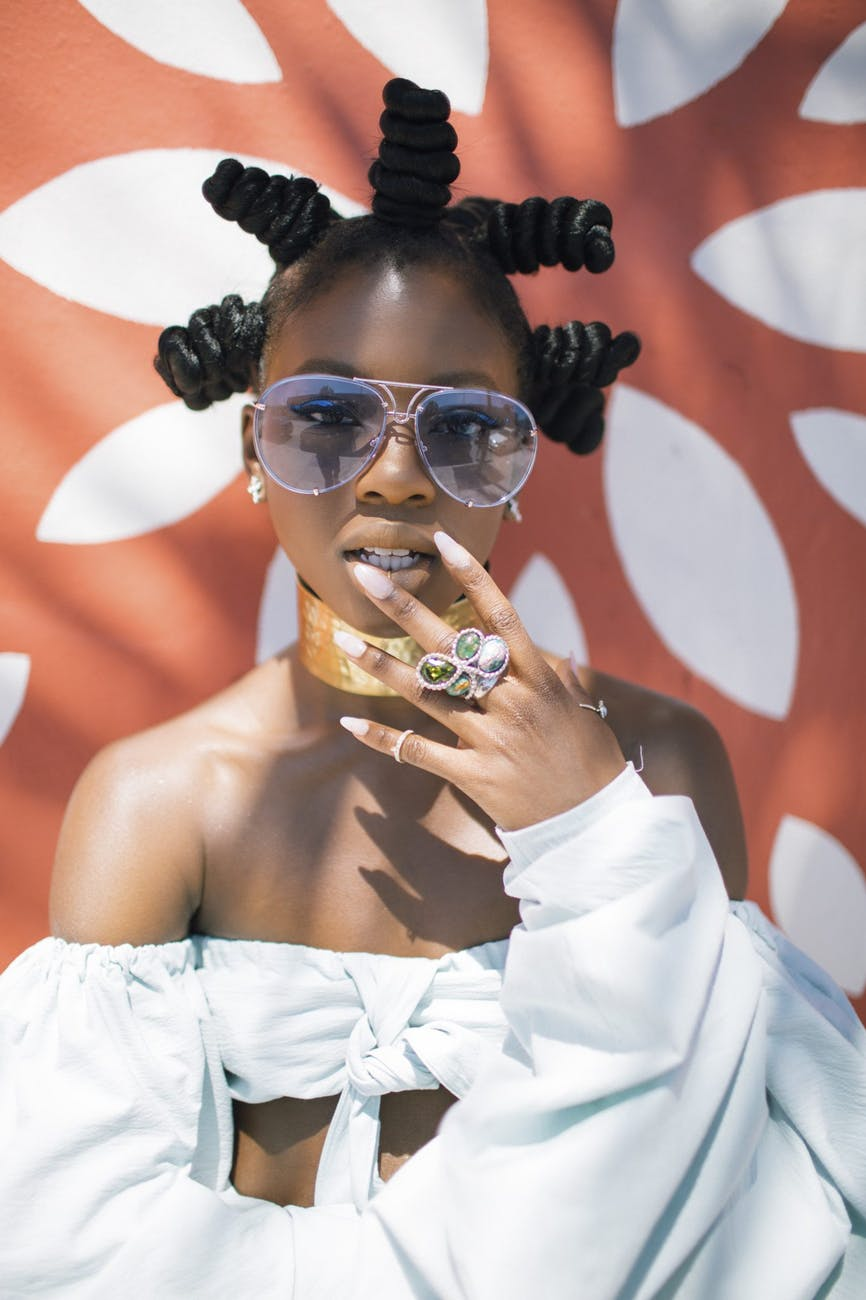 photo of woman in white crop top and silver colored framed aviator sunglasses