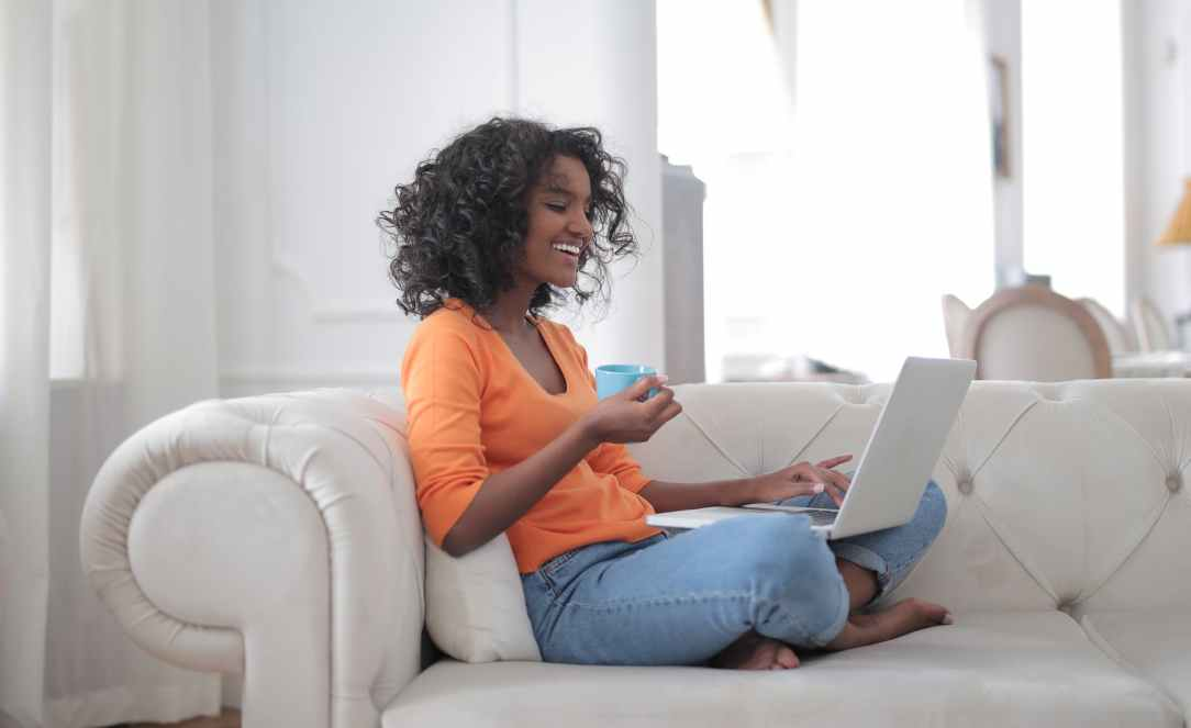 cheerful woman with cup of coffee surfing laptop