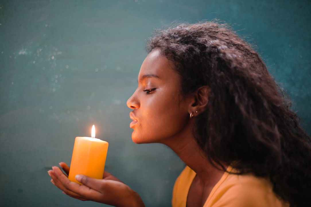 young ethnic lady holding burning candle in hands near wall at home