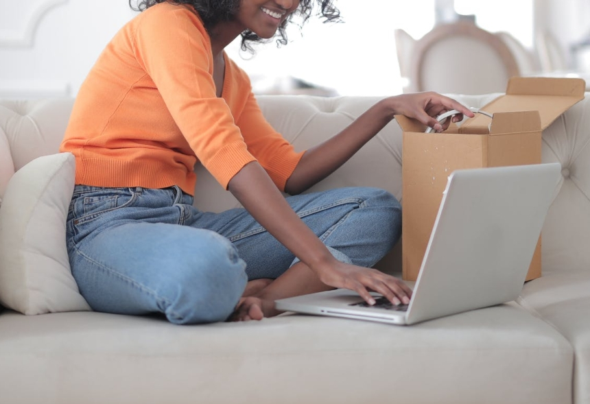 cheerful black woman opening box and using laptop